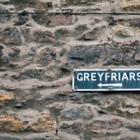 An old tourist direction sign on a stone wall in Edinburgh pointing to the Greyfriars Kirkyard.